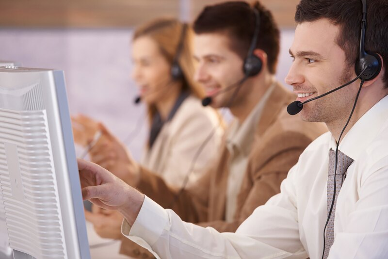 Young people working in call center, using headset and touch screen, smiling