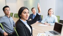 Confident young manager raising hand at workshop