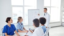 group of happy doctors or interns with mentor meeting