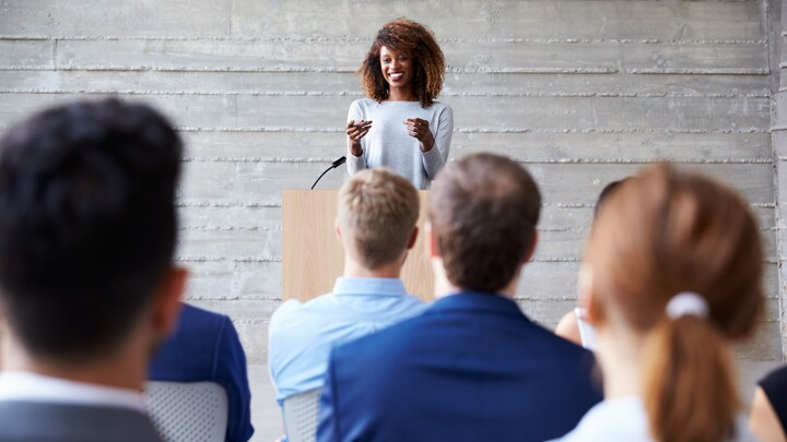 Businesswoman Addressing Professionals At Conference