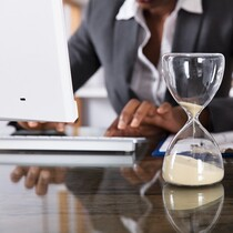 Close-up Of Hourglass In Front Of Businessperson Working In Office