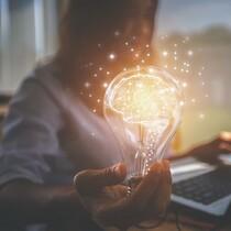 women holding lightbulb with conceptual brain