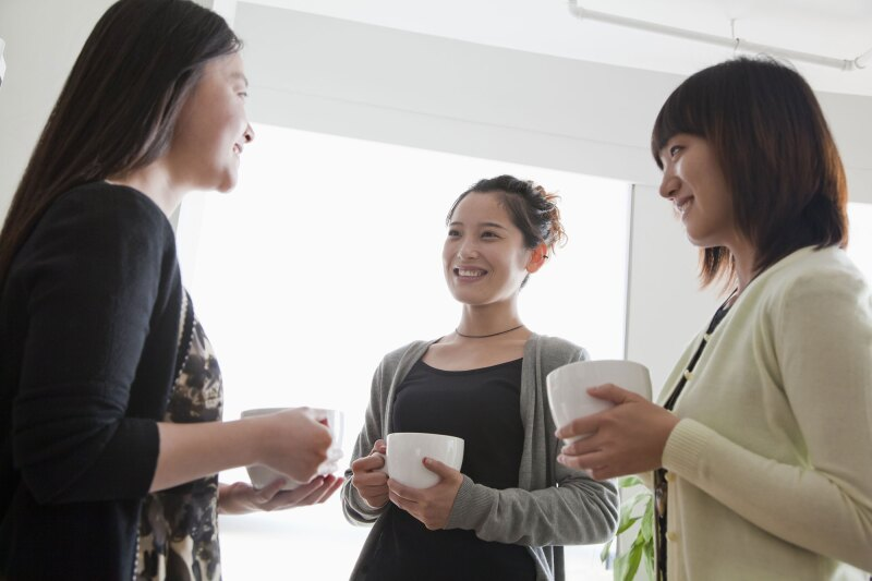 three asian staff memebers talk over coffee