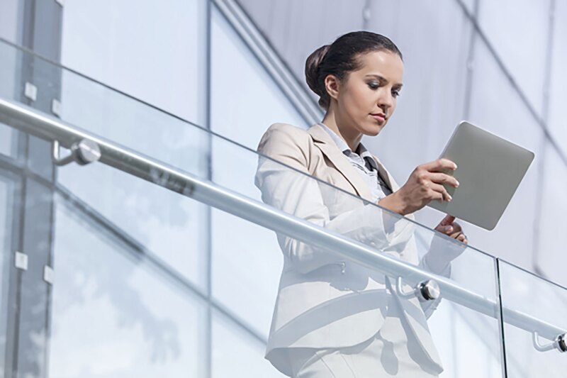 young business woman looking at her tablet over raililing