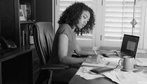 Busy black woman in office doing paperwork
