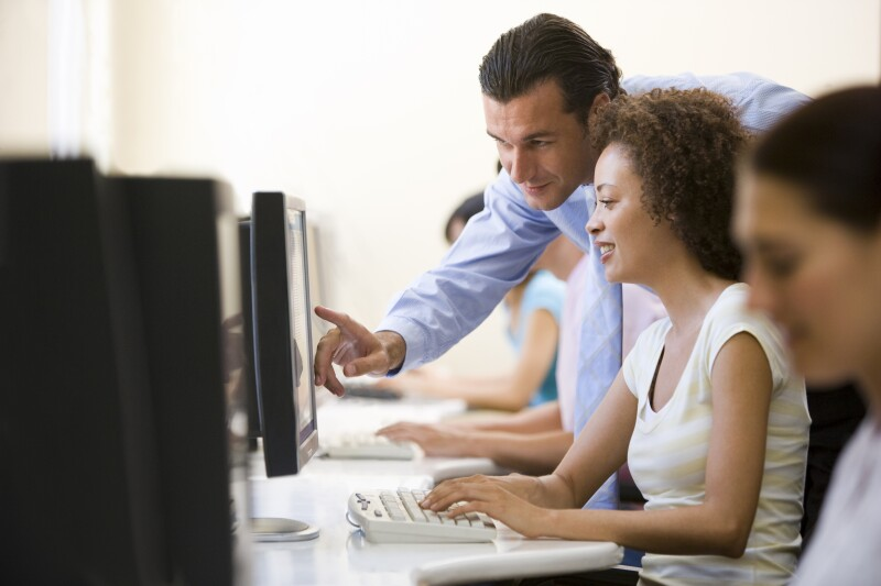 Man assisting woman in computer room 177279306