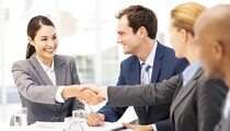 Happy Businesswomen Shaking Hands During Meeting