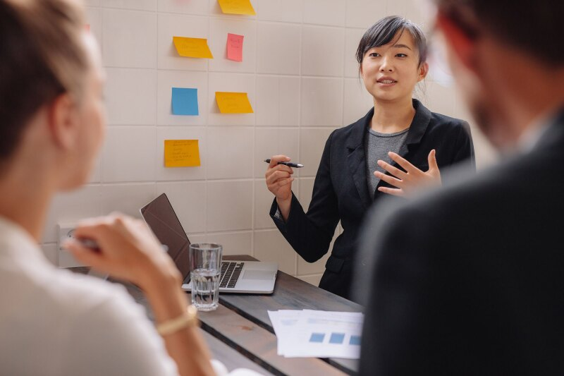 Asian businesswoman explaining her new business ideas to colleague