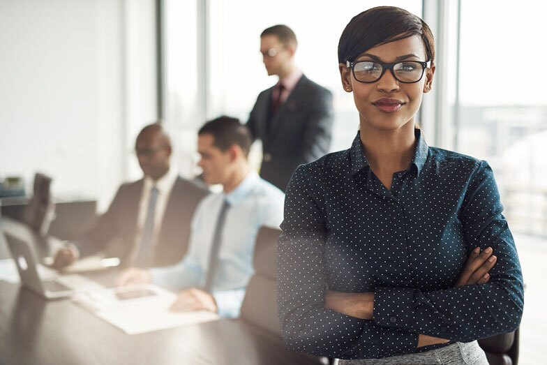 Confident young African businesswoman standing with folded arms
