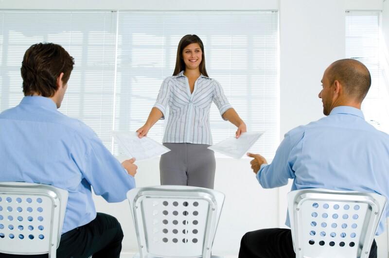 Businesswoman handing papers to businessmen