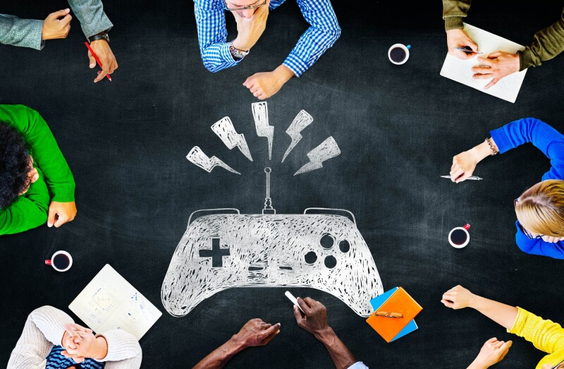 business people considering gamification around work table.jpg