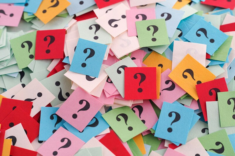 Pile of colorful paper notes with question marks