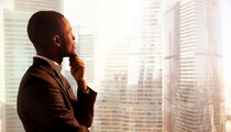 african-american-man-looking-out-window-corporate-buildings-shutterstock_653199826-78774.jpg