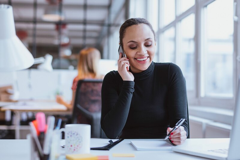 Happy young woman sitting at her desk working and answering a phone call