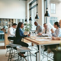 Smiling group of diverse businesspeople discussing paperwork together while having a meeting around a table in a modern office