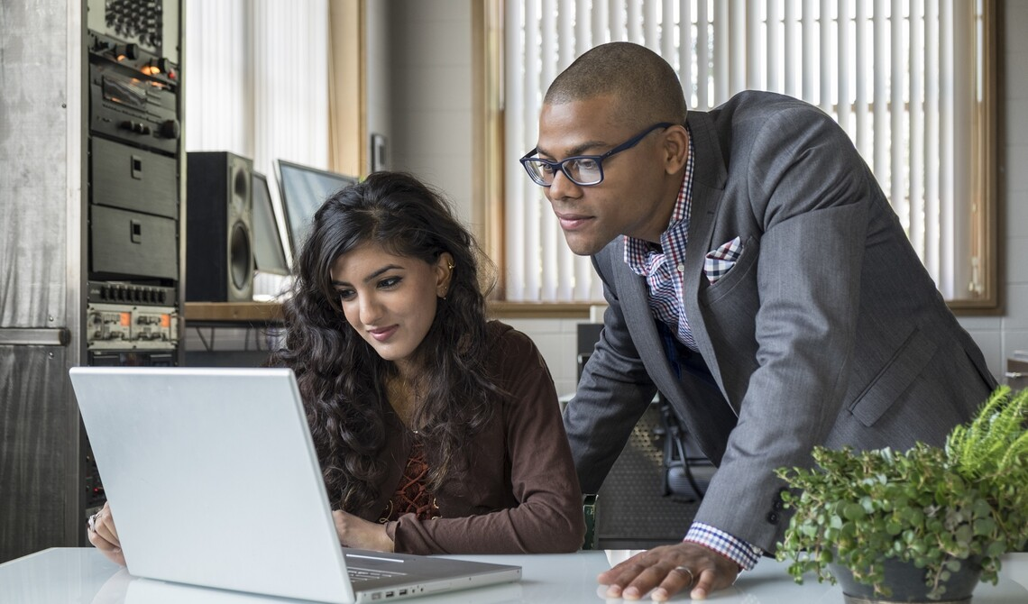 Young professionals working together in front of a computer