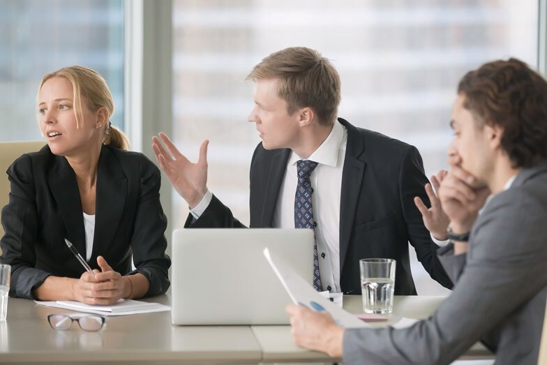 Furious boss scolding young frustrated interns with bad work results.