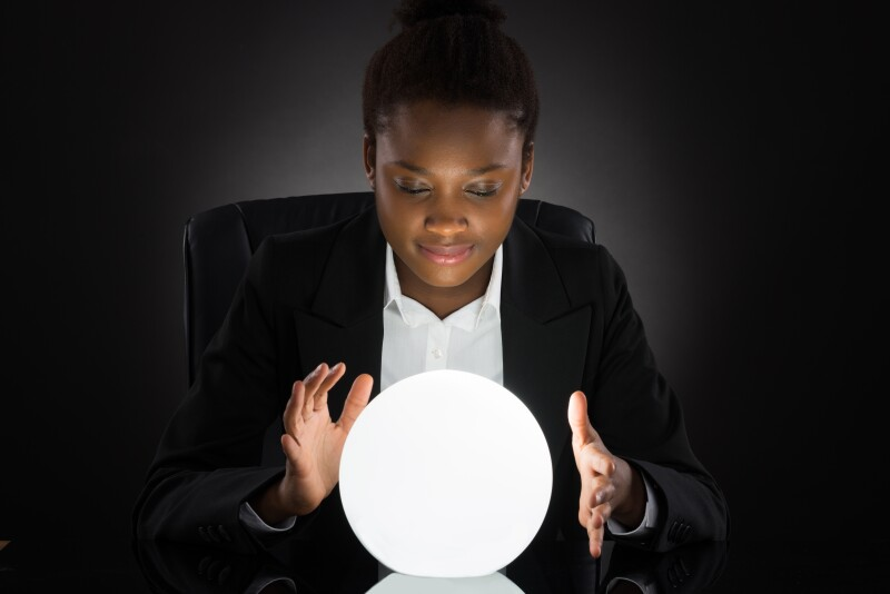 Young African Businesswoman Predicting Future With Crystal Ball On Desk