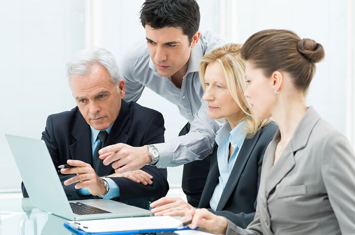 Team Of Business People Working Together On A Laptop