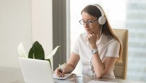Focused attentive woman in headphones sits at desk with laptop