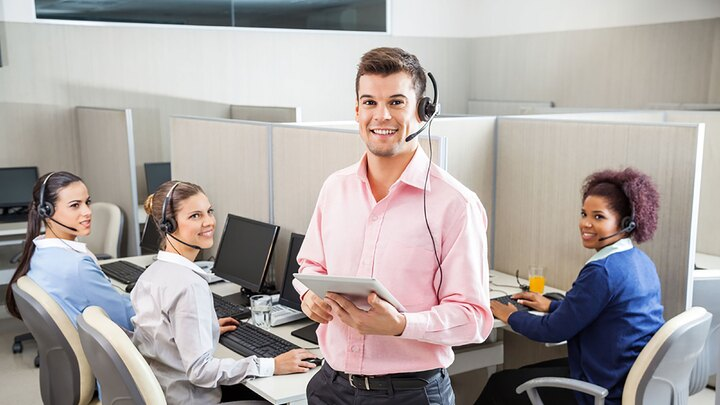 Portrait of young male customer service executive holding tablet computer while colleagues looking at him in call center