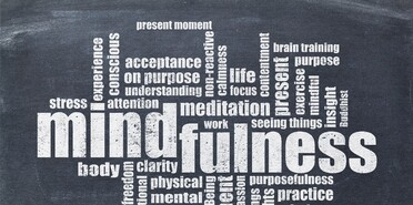 mindfulness word cloud in white chalk on a vintage slate blackboard