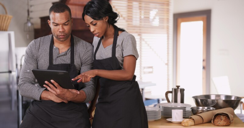 Small business owner showing employee new plan on tablet computer