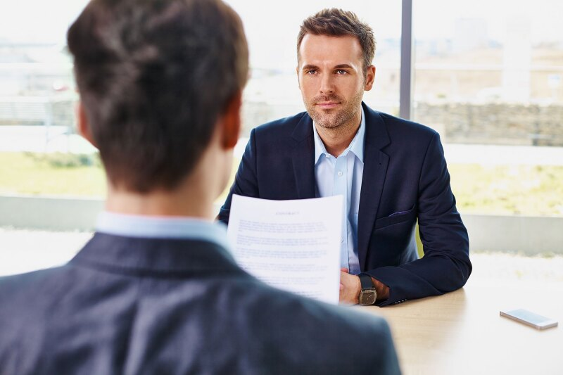 Job interview - candidate reading contract document, offer
