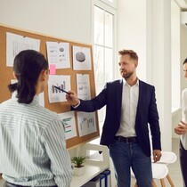 Business team analyzes sales graphs and charts, develops a new strategy, discussing work issues. Young project manager makes a suggestion or points out a mistake at the meeting. Concept of teamwork..jpg