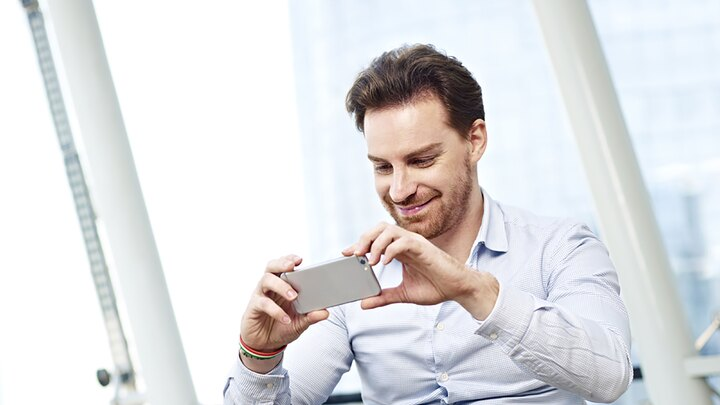 young caucasian business man looking at a picture or watching a video