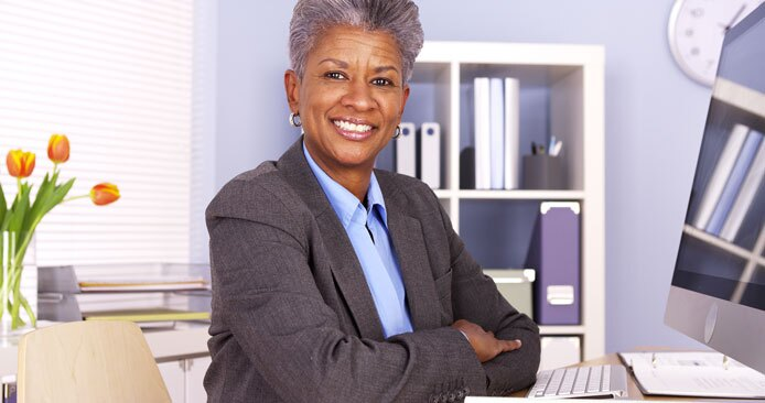 Mature African American businesswoman sitting at desk