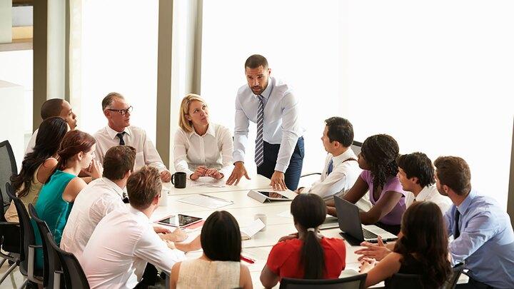 Businessman Addressing Meeting Around Boardroom Table