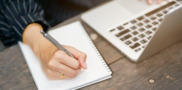 businesswoman hand writing content or something on notebook with using laptop at wooden table outside home
