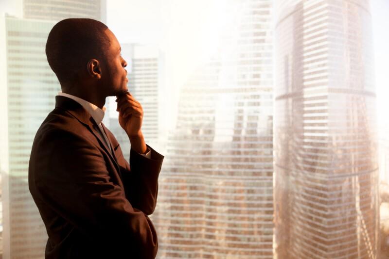 african-american-man-looking-out-window-corporate-buildings-shutterstock_653199826-78774.jpg