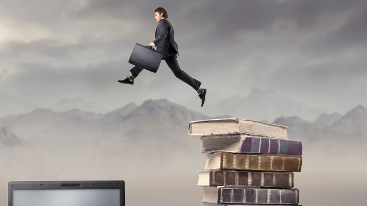 Businessman jumping from some books to a laptop